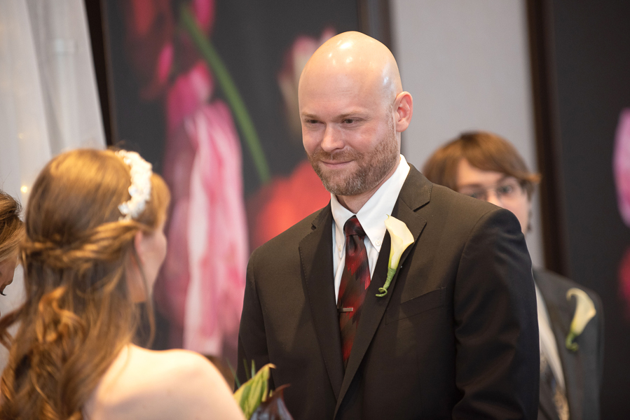 Groom smiling at bride during ceremony