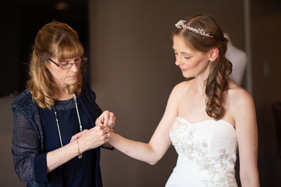 Mother of the bride helps her daughter with a bracelet before her ceremony at the Hilton Christiana