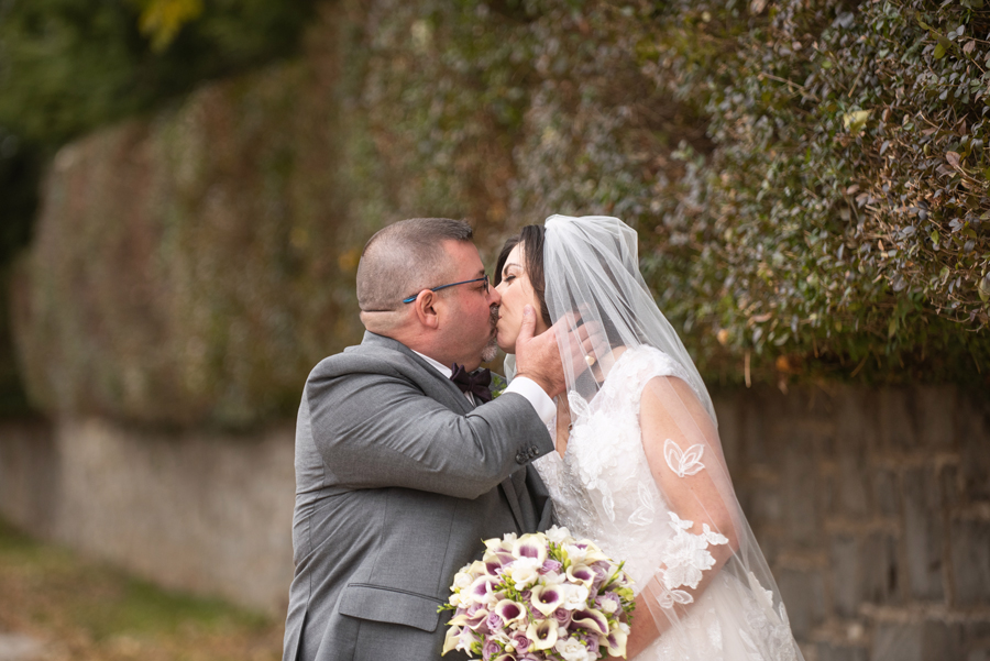 Groom pulls bride towards himself and kisses her