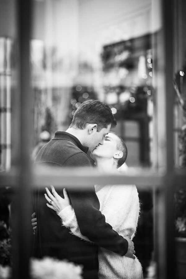 black and white image of engaged couple kissing taken through a window