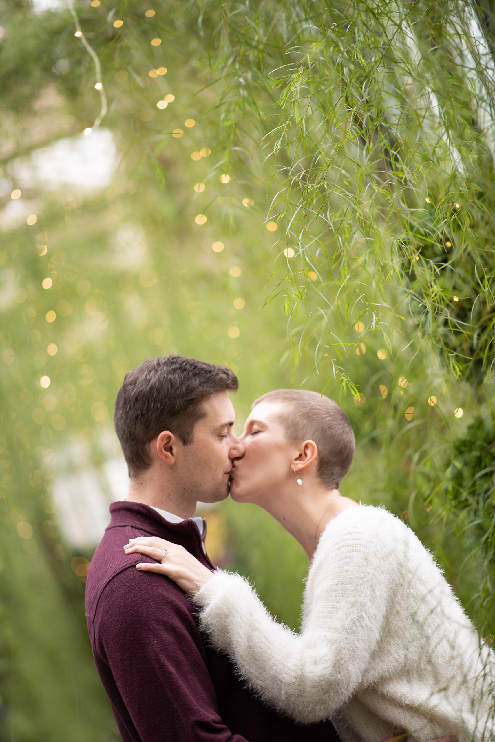 Kissing with beautiful green plants hanging behind
