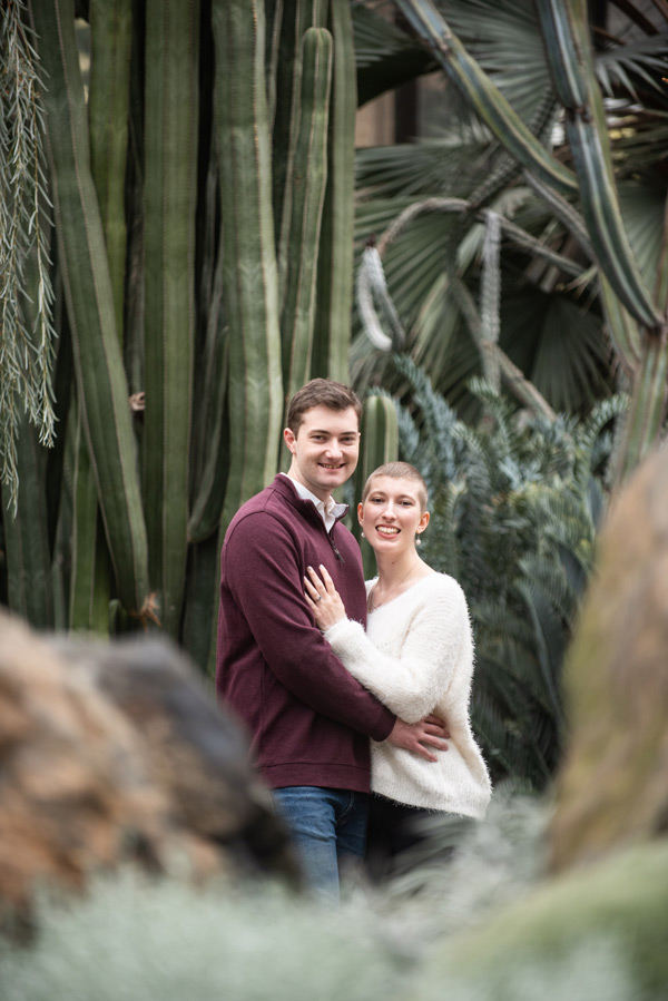 couple looks and smiles at camera they are surrounded by cacti