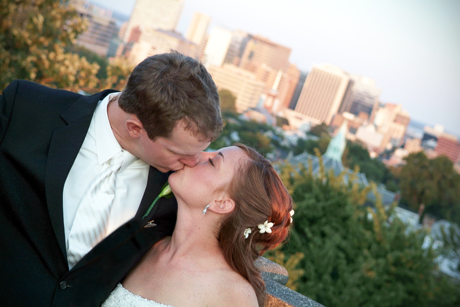 bride and groom kiss with Wilmington skyline in the background
