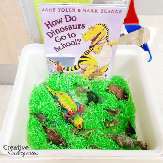 Dinosaur sensory bin for kindergarten classroom with book.
