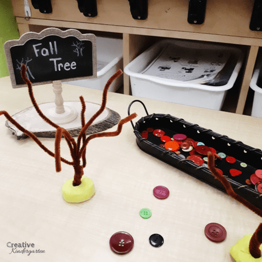 Fall tree fine motor sensory bin for kindergarten center. Thread buttons on pipe cleaner to practice fine motor skills.