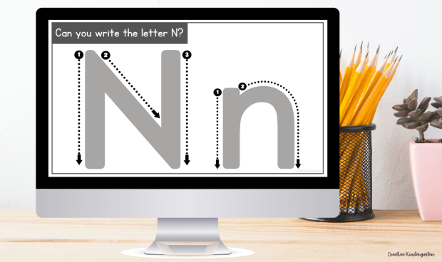 """""""Can you write the letter N?"""" with an uppercase and lowercase N graphic displayed on a computer screen. The background is a desk with pencils in a cup and a succulent plant in a pink pot."""