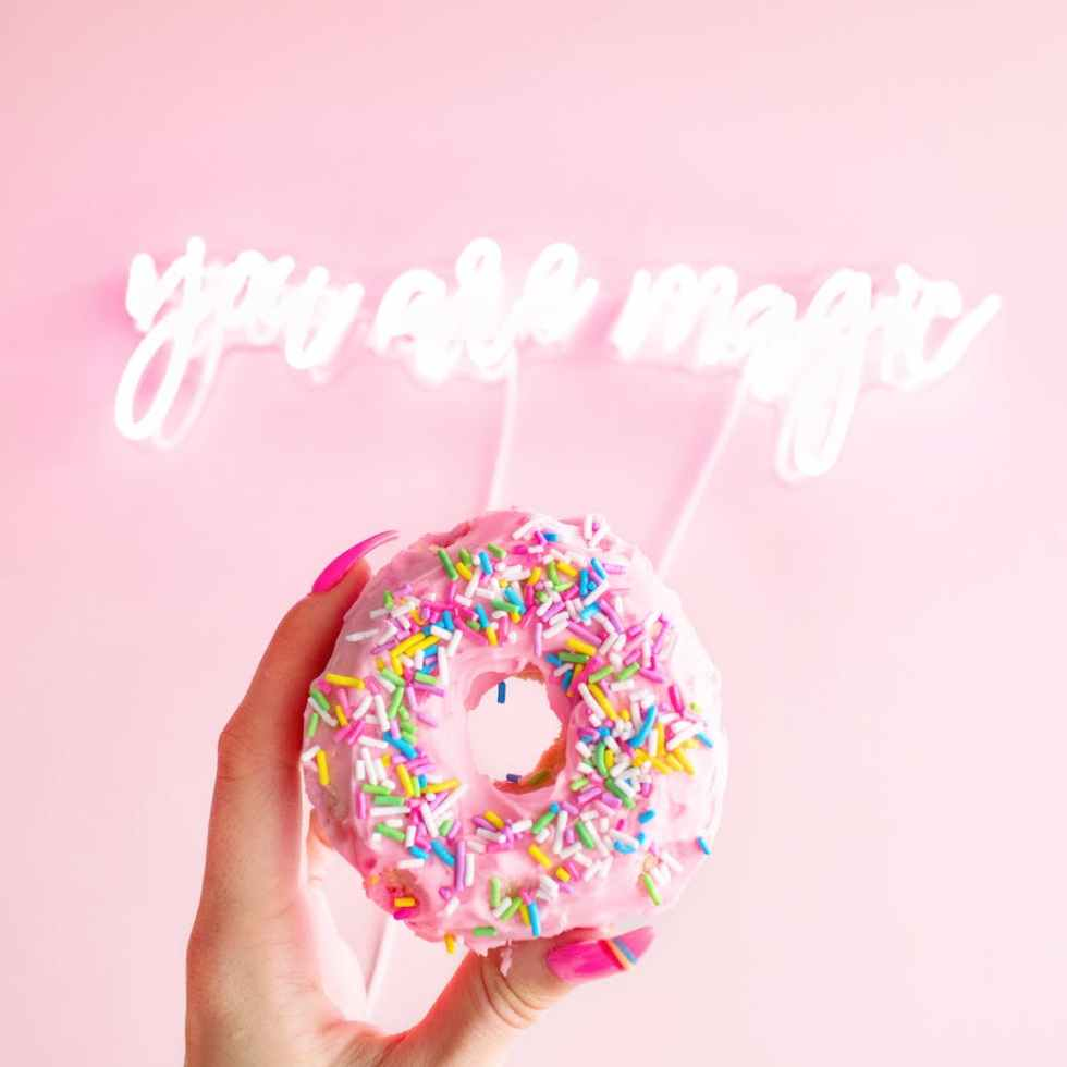 woman holding donut with sprinkles