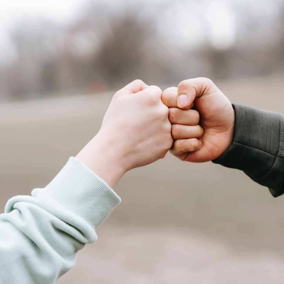 man and happy woman greeting each other with fist bump