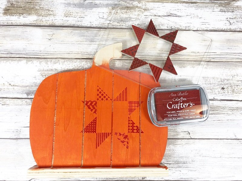 Creatively Beth load stamp with ink and stamp in a row across center of short wooden pallet pumpkin