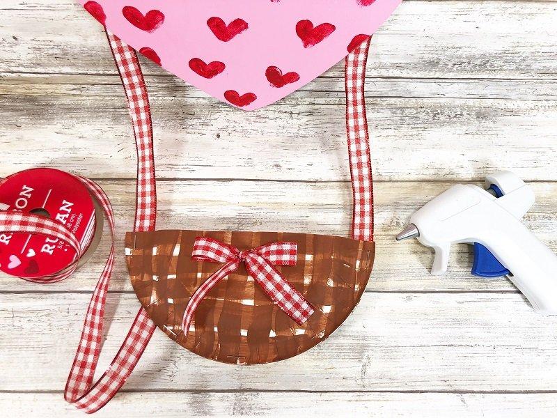Add bow to basket front Hot Air Balloon Valentine Mailbox Creatively Beth #creativelybeth #dollartreecrafts #kidscrafts #valentinesdaycrafts