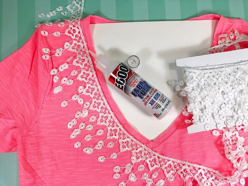 Girl wearing a coral colored tee shirt with white lace fringe trim attached to the neckline with fabric glue. #creativelybeth #upcycled #clothing #lace #tshirt #teeshirt