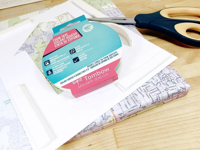 Attach house cut out to recycle map covered canvas with foam tape Creatively Beth #creativelybeth #upcycled #recycled #crafts #maps