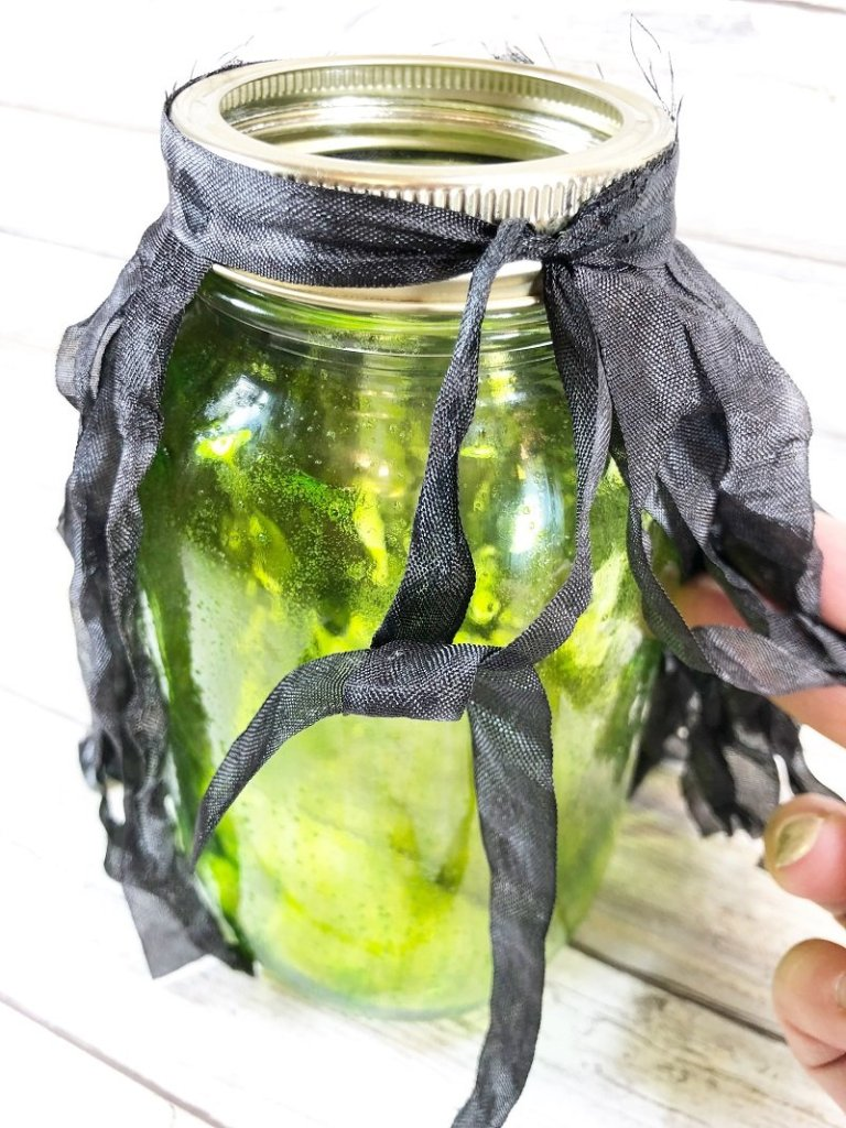Tie witch's hair around neck of mason jar and secure with a knot Creatively Beth #creativelybeth #masonjar #witch #halloween #craft #creativecrafts