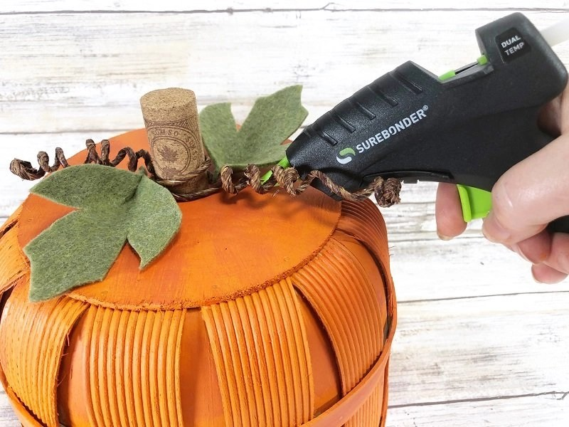 Hot glue stem, vines and leaves to the top of the basket pumpkin Creatively Beth #creativelybeth #dollartree #craft #falldecor #bushelbasket #pumpkin #craft