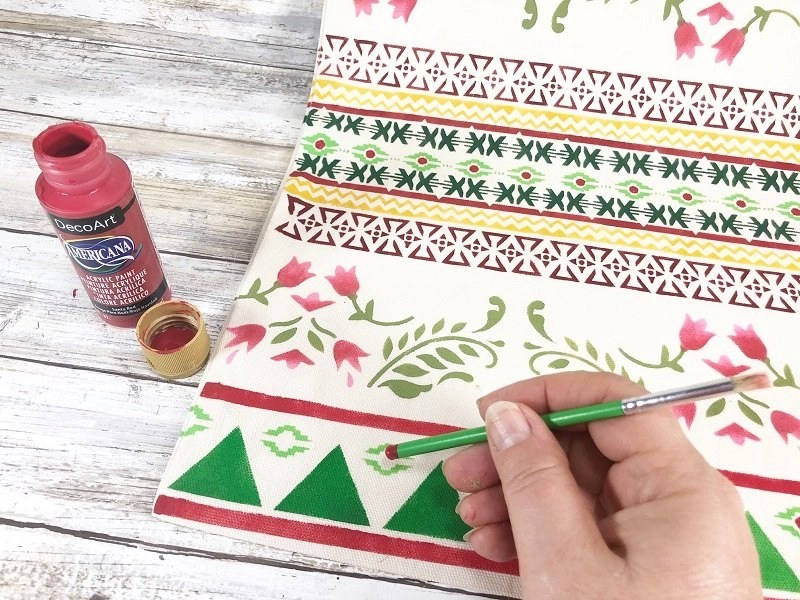 Add dots to the center of some of the designs with the end of a paintbrush dipped in paint Creatively Beth #creativelybeth #fairfieldworls #uglychristmassweater #pillowparty2020 #stenciled #decoart