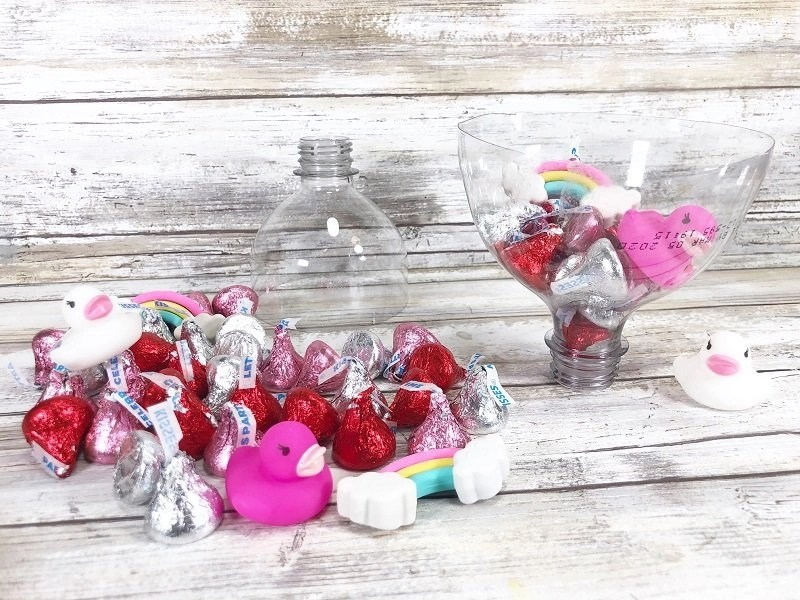 Fill plastic bottle tops with chocolate kisses and small toys Creatively Beth #creativelybeth #valentinesday #hersheykiss #recycledcrafts