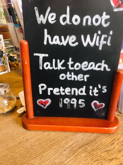we don't have wifi, talk to each other, pretend it's 1995 on a blackboard sign with two hearts