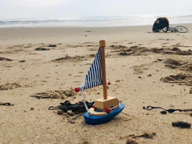 a toy boat on a beach with a bike in the background