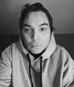 Black and White photo of Scott Benesiinaabandan wearing a hoodie