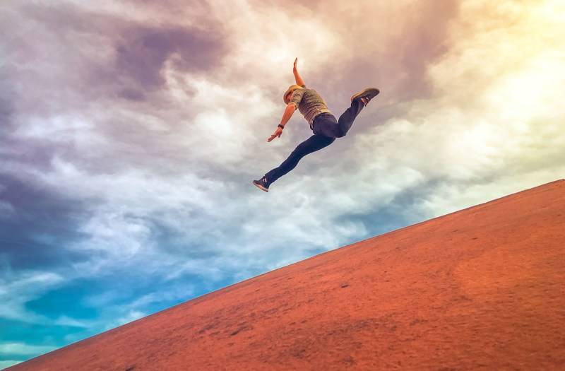 Man Jumping Down A Hill