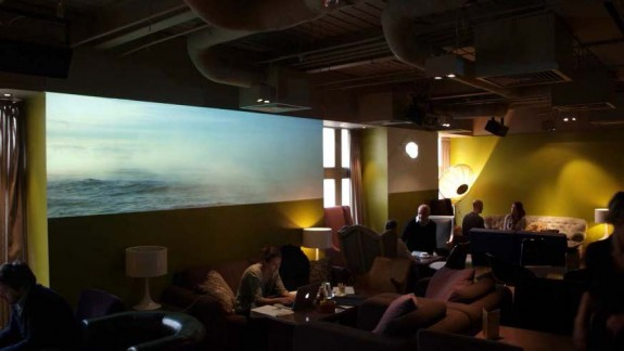 For the members' lounge of The Hospital Club in London, Open Gallery created a multiple-screen installation of video art.  Works by seven artists are featured on three large-scale projections and three small LCD monitors. Photo: Open Gallery