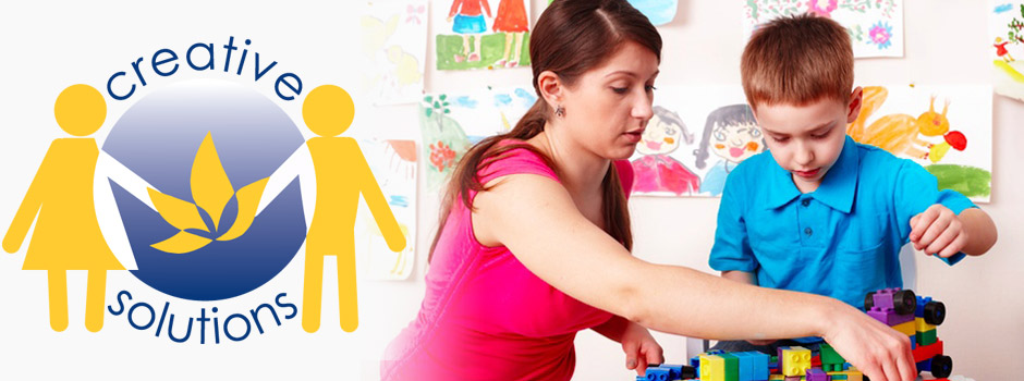 lady working with a boy and his toy blocks