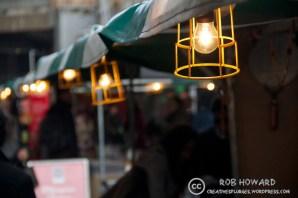 row of lightbulbs above market stalls