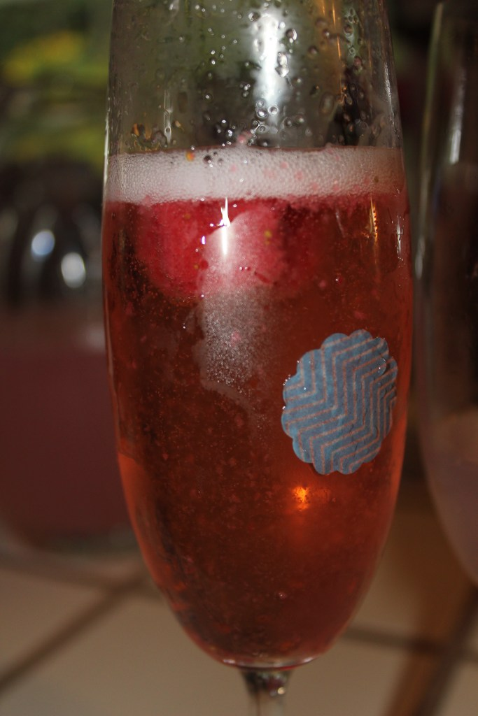 Strawberry star in pink sparkling wine with a washi tape drink marker.