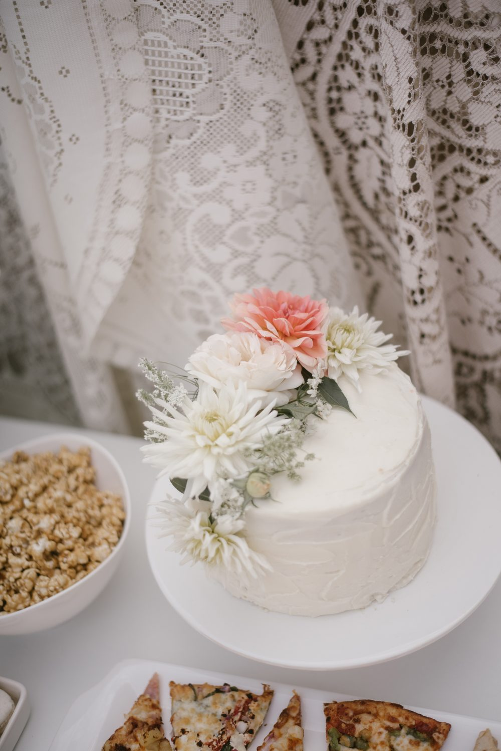 White floral cake at lace and boho baby shower | White Boho Baby Shower