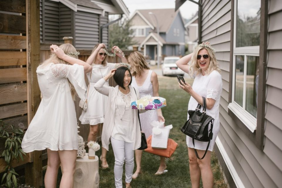 Guests putting on babies breath flower crowns at baby shower | White Boho Baby Shower