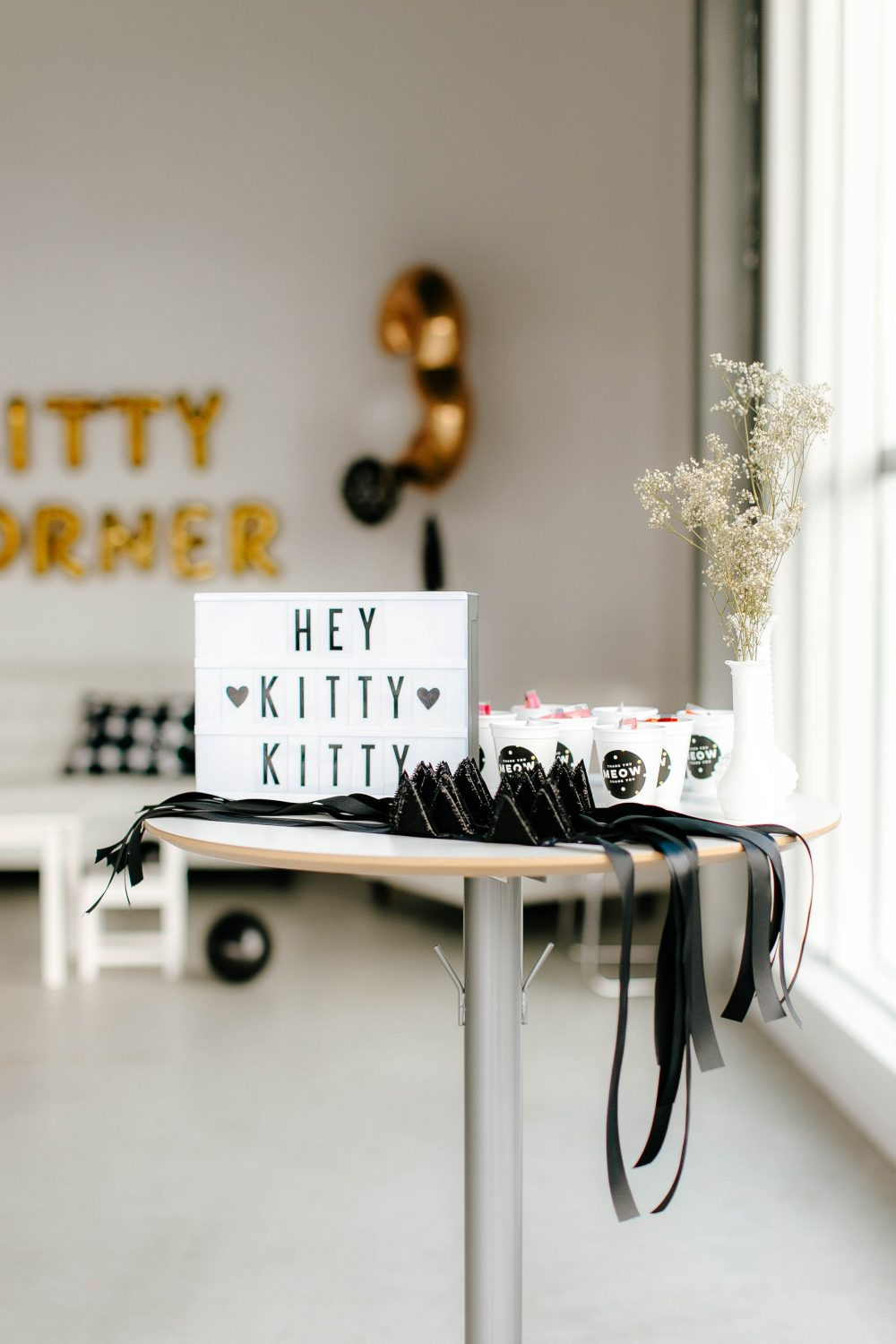 DIY Kitty Cat ears and welcome sign for guests at Black, White and Gold Kitty Cat Themed Girl's Birthday Party