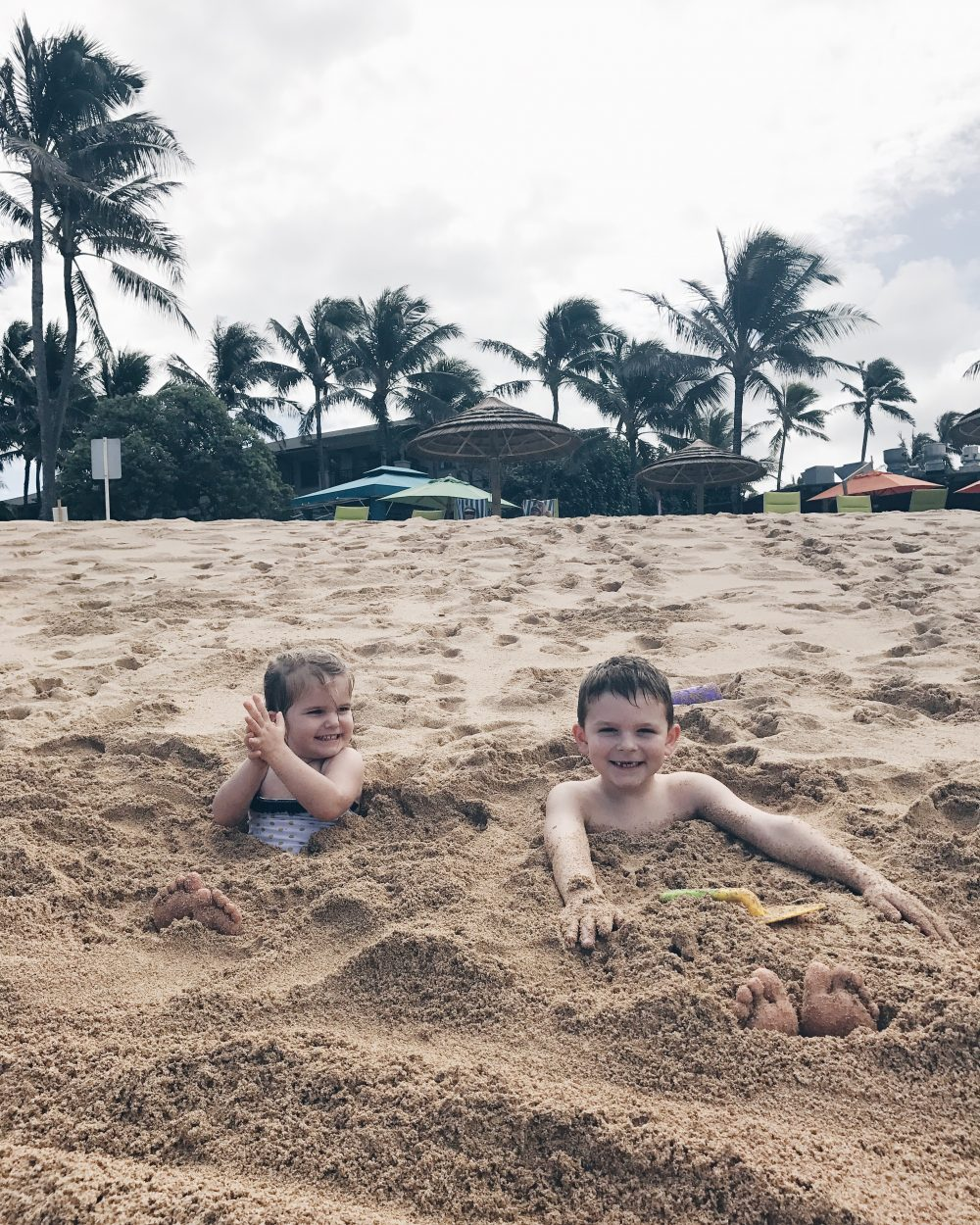 Kids burried in the sand on Hawaii's North Shore