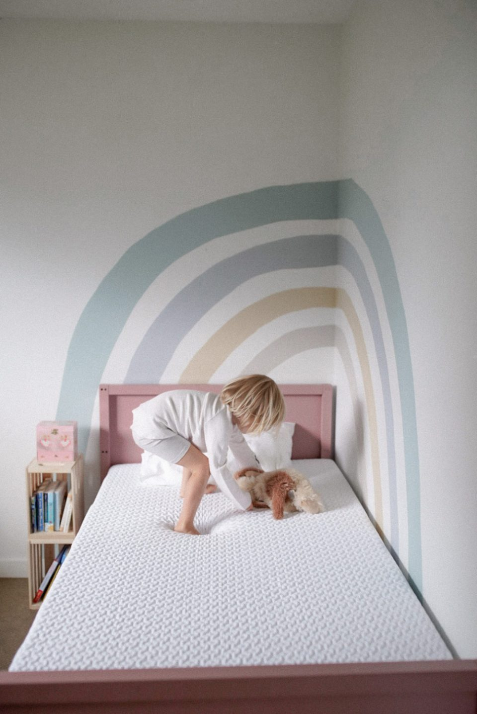 Little girls room with large rainbow painted on the wall