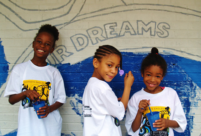 Three girls in white T-Shirts hold blue cups and paint brushes in from of a brick wall. They are in the process of painting a mural on that wall. Photo courtesy of Mural Arts Philadelphia, Philadelphia, PA.