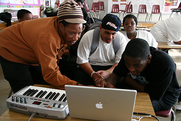Three young men are huddled around a laptop connected to a keyboard, while a man standing next to them is explaining what they're seeing. Photo courtesy of Performing Arts Workshop, San Francisco, CA.