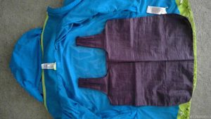 old shopping bag laying flat on top of old jacket to create pattern for upcycled bag