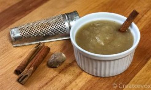 spiced applesauce in a small bowl with a cinnamon stick