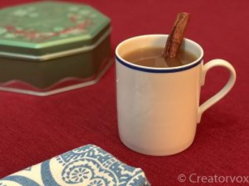 mug of hot apple cider with a cinnamon stick in it