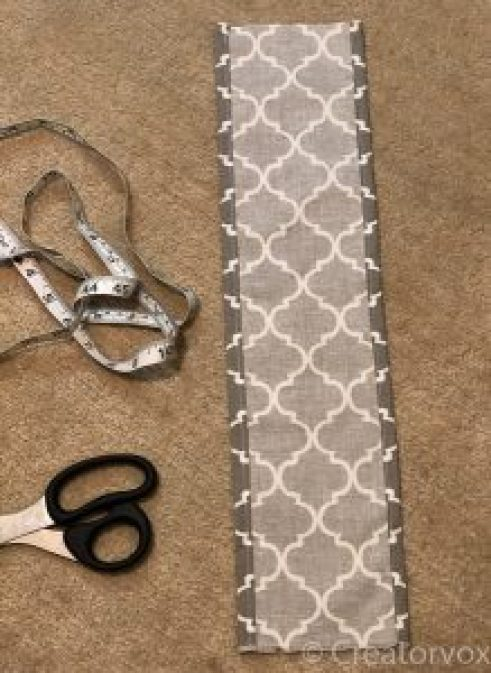 fabric for a bag with the sides pinned for seaming next to scissors and a tape measure