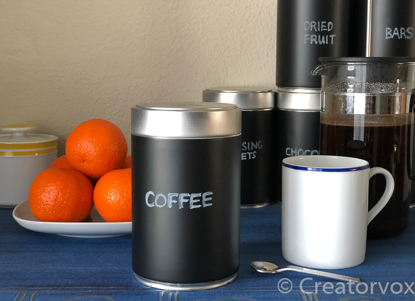 upcycled coffee can with chalkboard label, white mug, oranges, similarupcycled cans in background