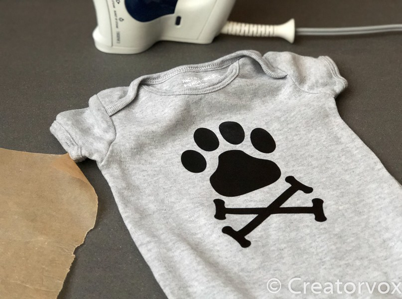 grey onesie with a printed graphic of a dog paw-print and crossbones