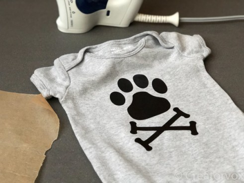 dog paw-print and crossbones on grey onesie