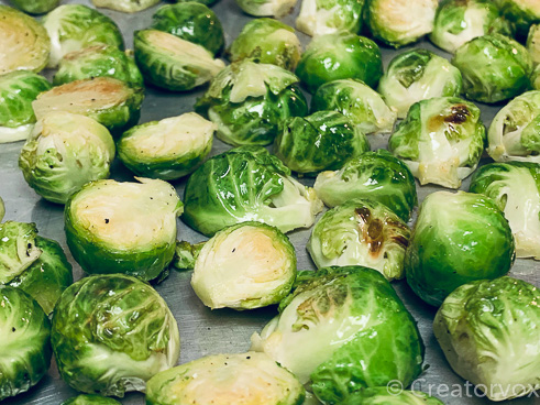 Roasted Brussels sprouts halfway through the cooking process being tossed so the browned sides are up