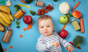 baby surrounded with fruits and vegetables on blue blanket, healthy child nutrition