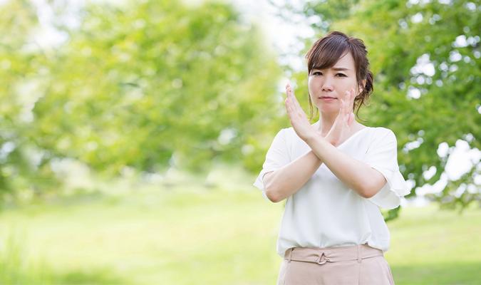 腕でバツのジェスチャーをしている女性