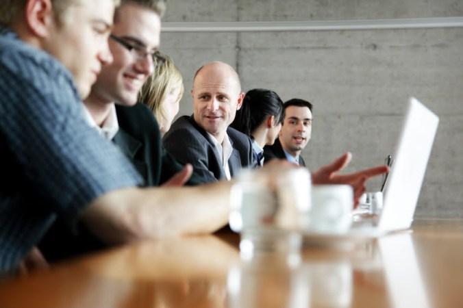 Businesspeople on Laptops in Meeting