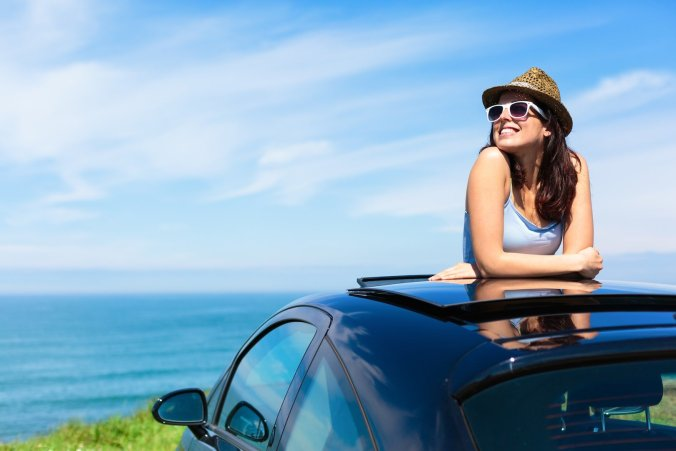 Woman Peering Out of Car Moonroof Along Water
