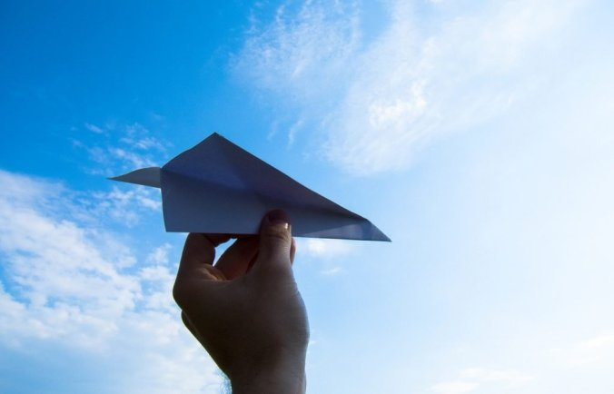 Paper Airplane Held in Hand