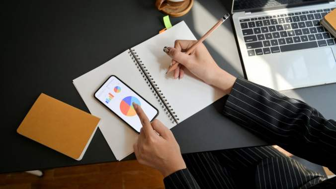 Writing in Paper Notebook with Pencil alongside Phone and Laptop