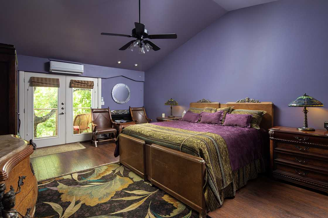 wide shot of purple walled bedroom, purple bed, a fireplace with round mirror above